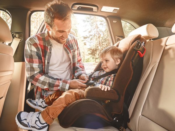 Father is adjusting child's car seat, smiling to his son. Side view