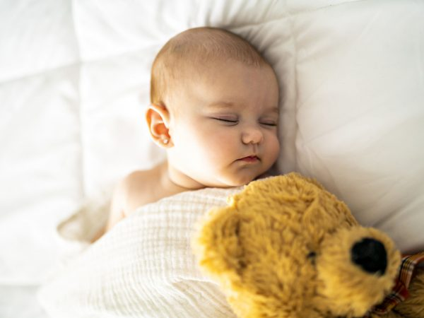 4 month baby sleeping on a white bed at home
